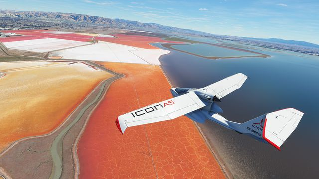 A white Icon A5, a two-seater aircraft with folding wings and a push-propeller configuration, flies over an arid salt pan on the edge of the ocean. The ground is brightly colored red and the sky is clear and blue.