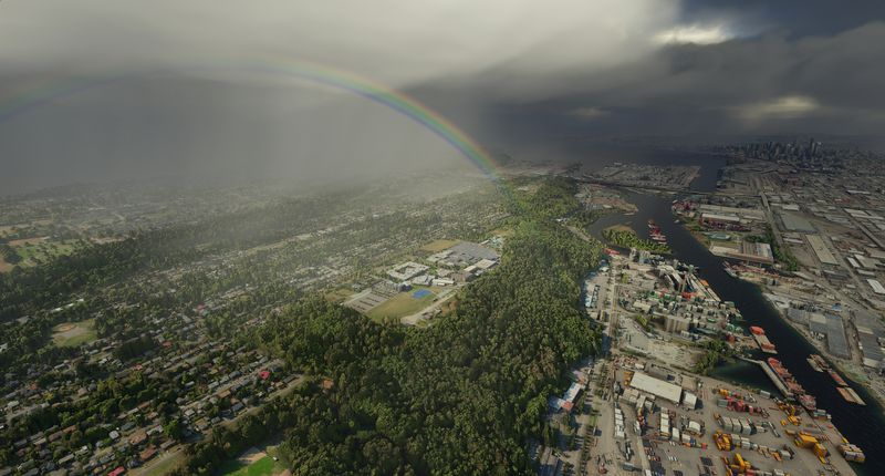 A rainbow emerges at the edge of a storm cloud. Below, green trees and grass border an industrial area along a river. From an early alpha of Microsoft Flight Siumulator.