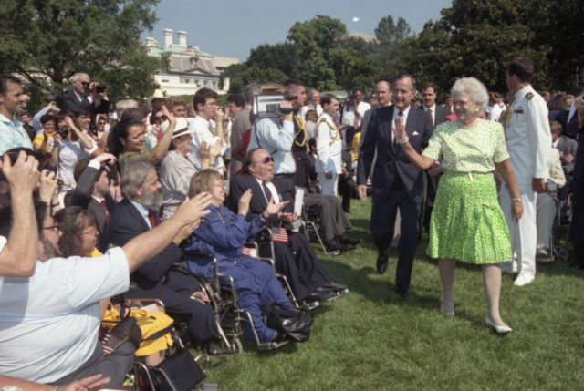Back in 1990, President George H.W. Bush and Barbara Bush receive applause by some of the 2,000 people from major disability groups who gathered to witness the signing of the Americans with Disabilities Act (ADA). (How times have changed—take a gander at that video camera!)