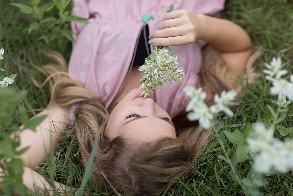 Girl laying in grass smelling flowers dark and moody edit