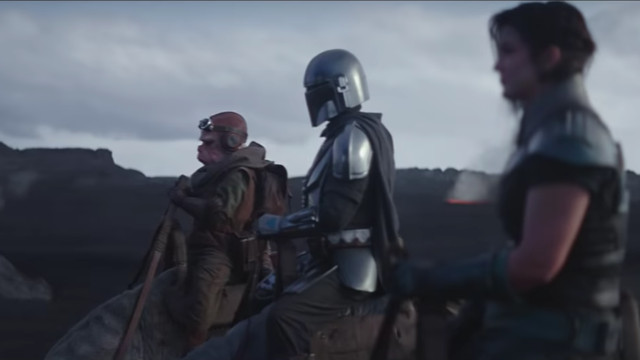 The Mandalorian and two other mounted characters against a desert landscape