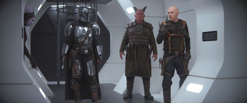 the mandalorian, a devil man, and bill burr stand on a prison ship